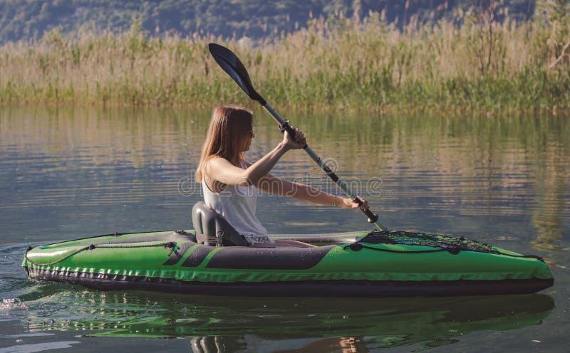 Junge Frau, die auf dem See Kayak f?hrt lizenzfreie stockfotos