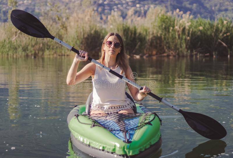 Junge Frau, die auf dem See Kayak f?hrt stockfotografie