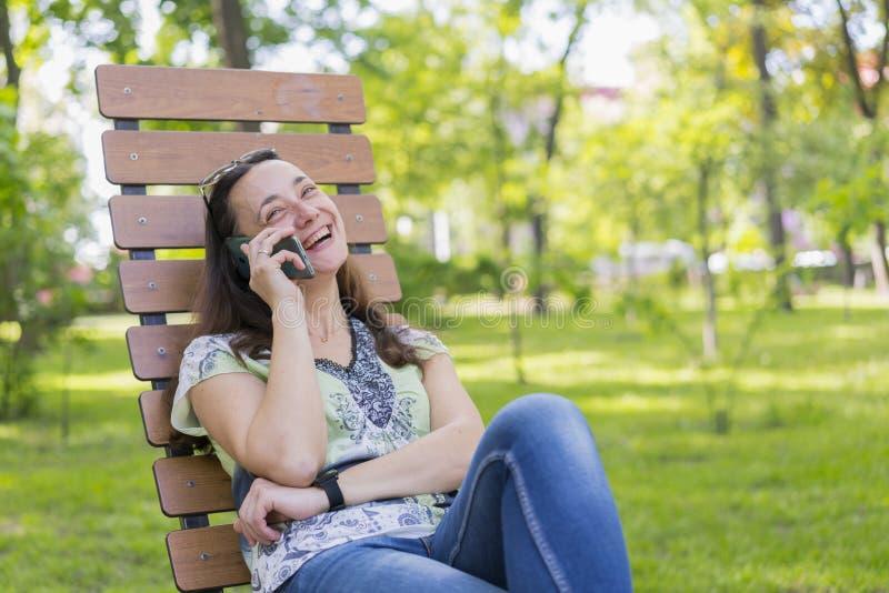 Junge Frau, die auf dem Smartphone spricht und im Park auf der sch?nen weiblichen Entspannung der Bank auf einer Parkbank und der stockbilder
