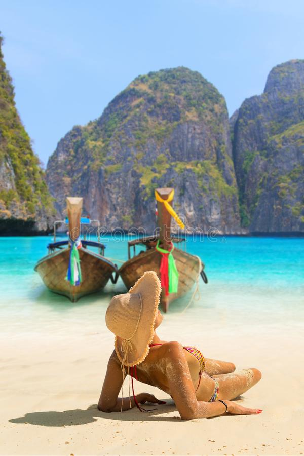 Junge Frau, die auf dem Strand bei Maya Bay auf Phi Phi Leh Isla sitzt stockfoto