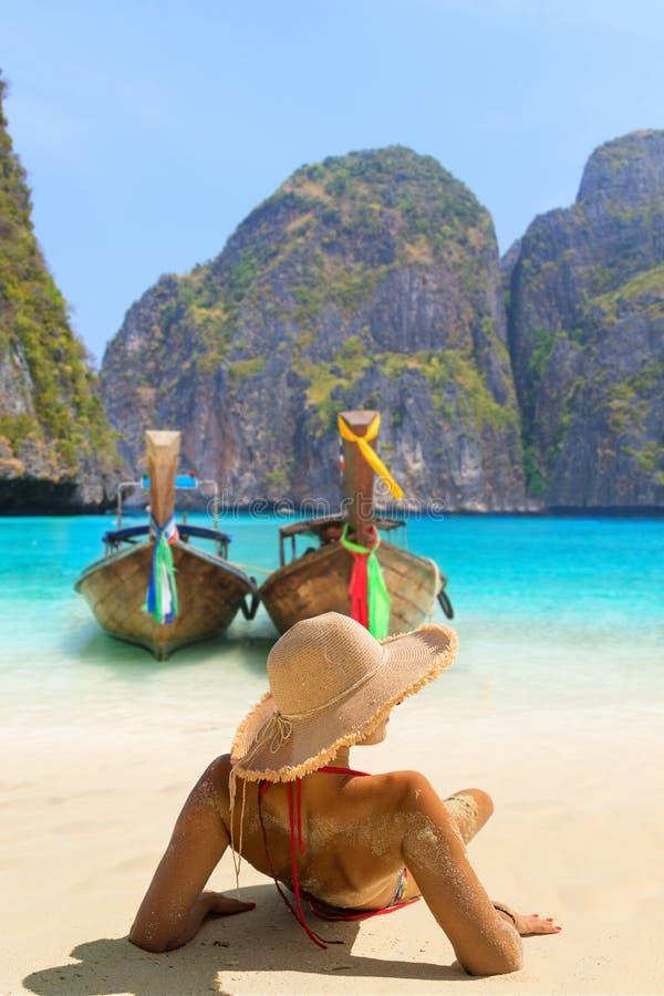 Junge Frau, die auf dem Strand bei Maya Bay auf Phi Phi Leh Isla sitzt lizenzfreie stockfotografie