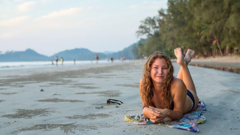 Junge Frau, die auf dem Strand liegt stockfotografie