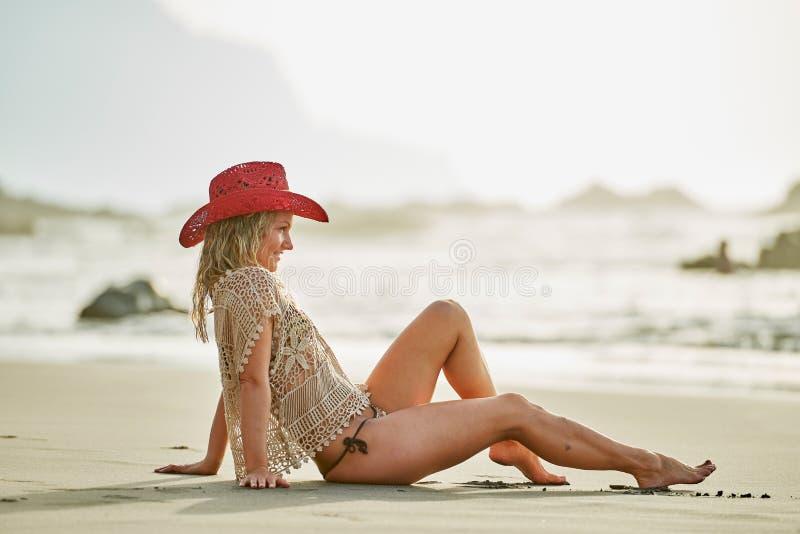 Junge Frau, die auf dem Strand am Sommertag sich entspannt stockbild
