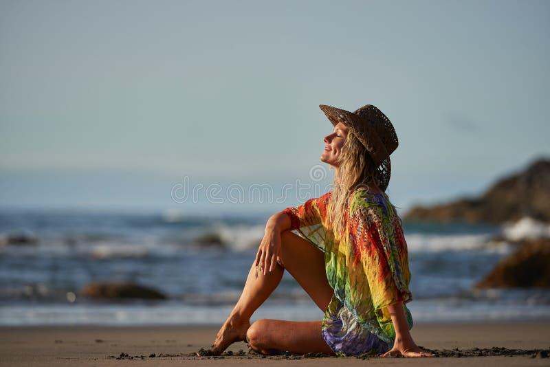 Junge Frau, die auf dem Strand am Sommertag sich entspannt stockfoto