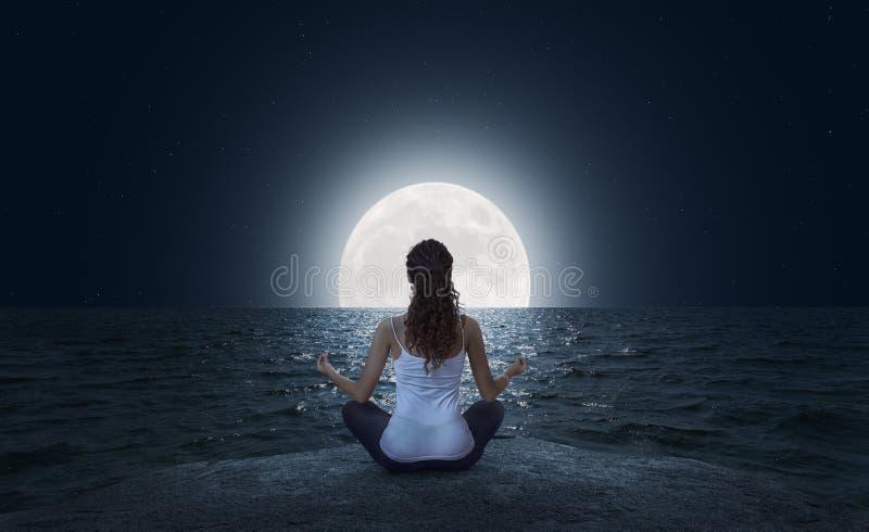 Junge Frau, die auf dem Strand am Vollmond meditiert stockfotografie