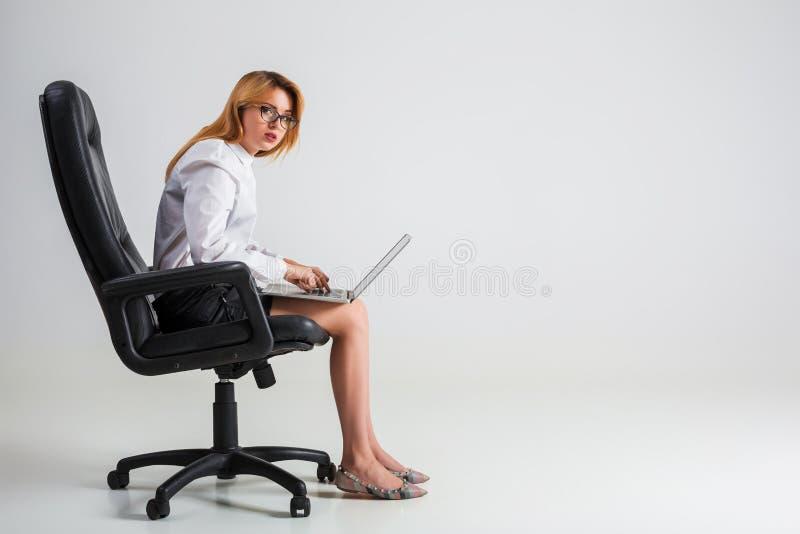 Junge Frau, die auf dem Stuhl sitzt und Laptop verwendet lizenzfreie stockbilder