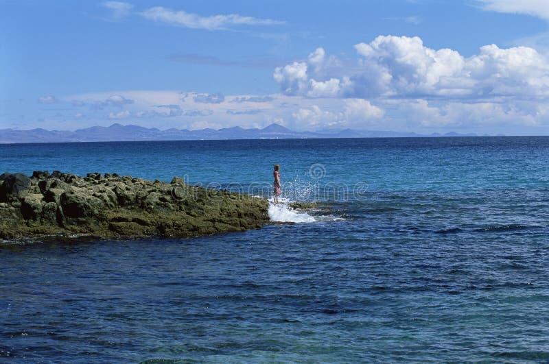 Junge Frau, die auf den Felsen, heraus schauend zum Meer steht stockfotos