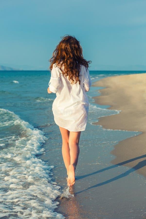 Junge Frau, die auf den Strand läuft stockfoto