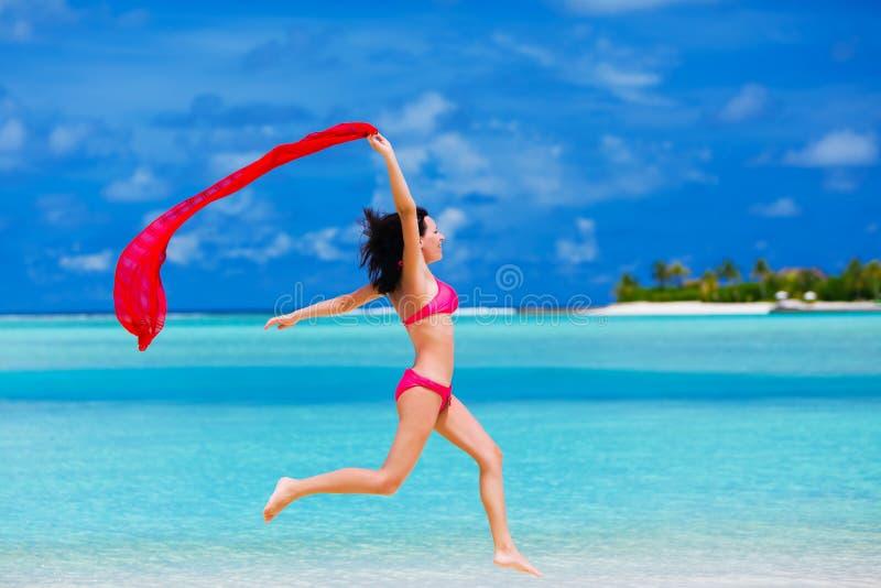 Junge Frau, die auf den Strand mit einem roten Schal springt lizenzfreie stockfotos