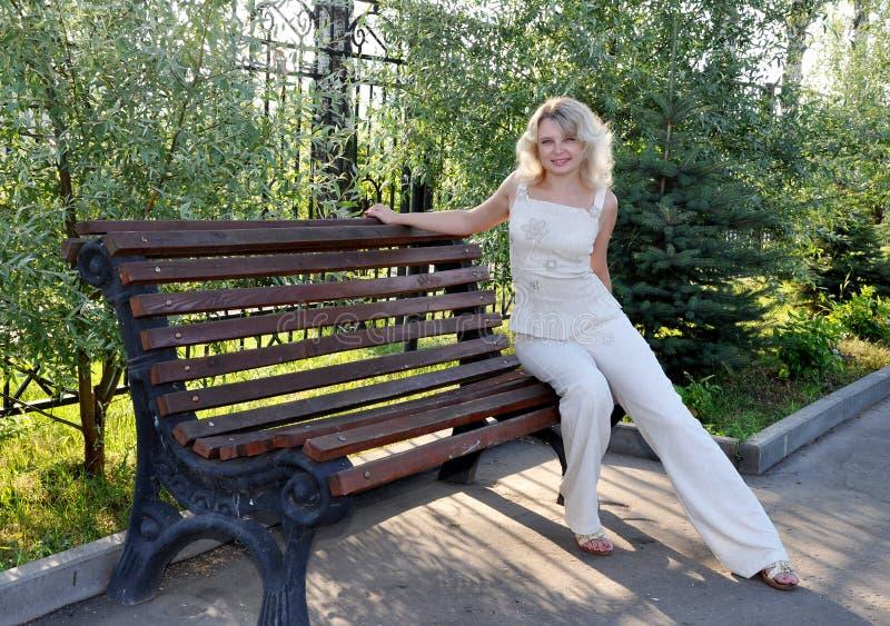Junge Frau, die auf der Bank sitzt stockfoto