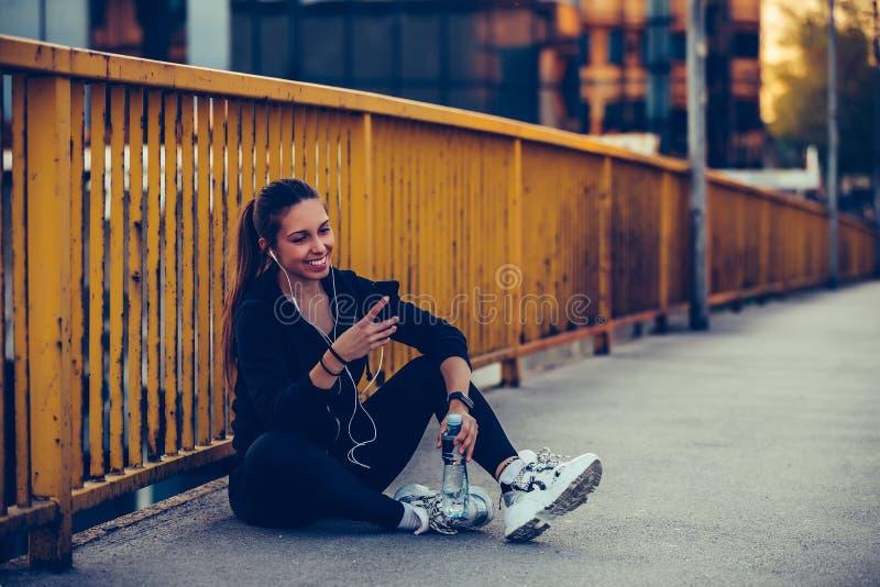 Junge Frau, die auf der Brücke unter Verwendung ihres intelligenten Telefons sich entspannt und Musik hört lizenzfreie stockbilder