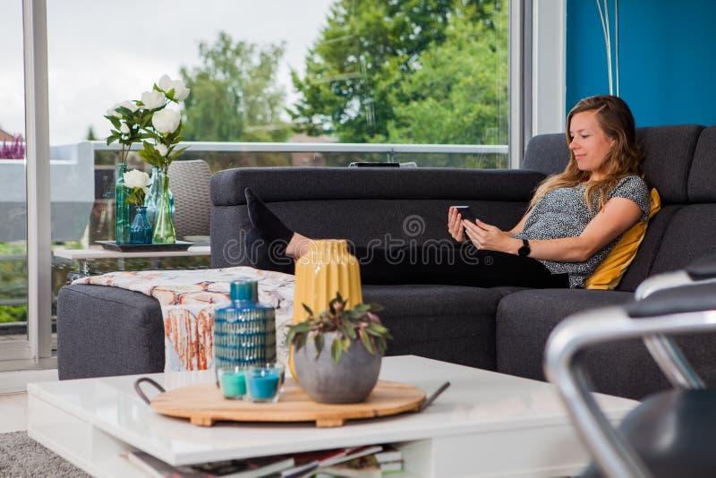 Junge Frau, die auf der Couch liest ein ebook kühlt lizenzfreies stockbild