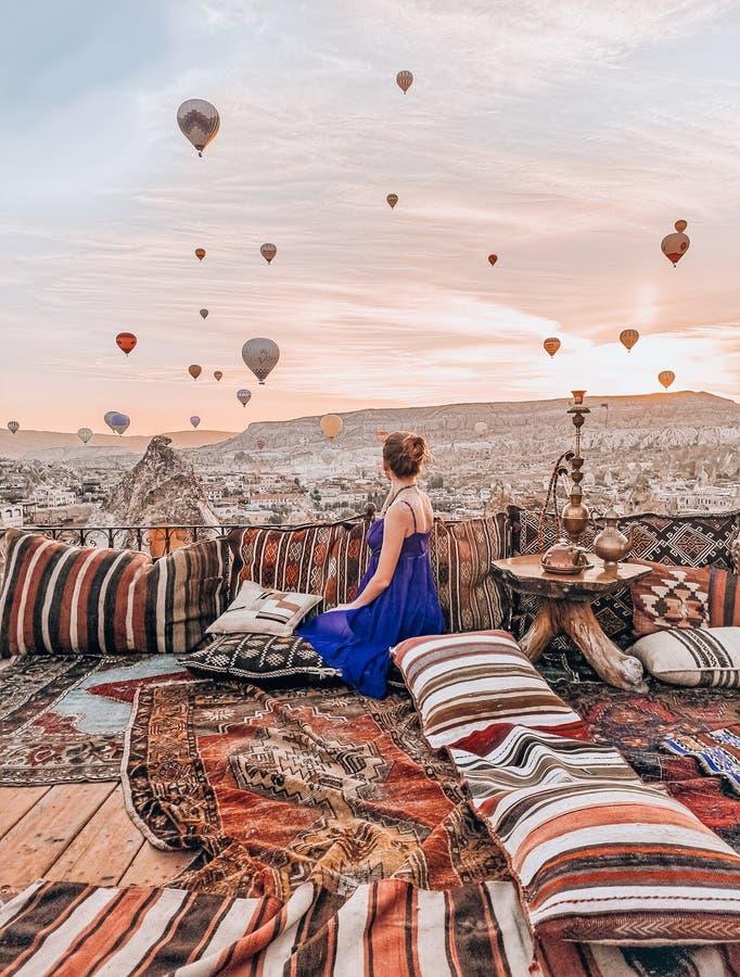 Junge Frau, die auf der Terrasse in aufpassendem Sonnenaufgang Cappadocia und in den Luftballonen sitzt stockfotos
