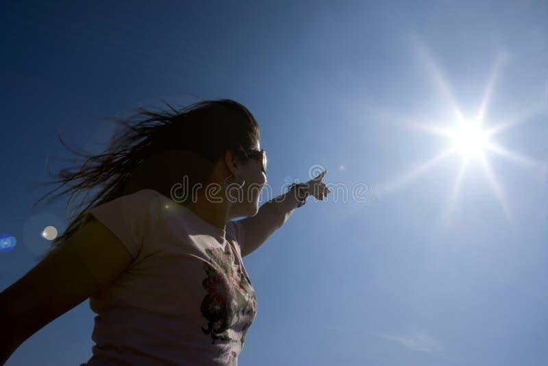 Junge Frau, die auf die Sonne zeigt lizenzfreies stockbild