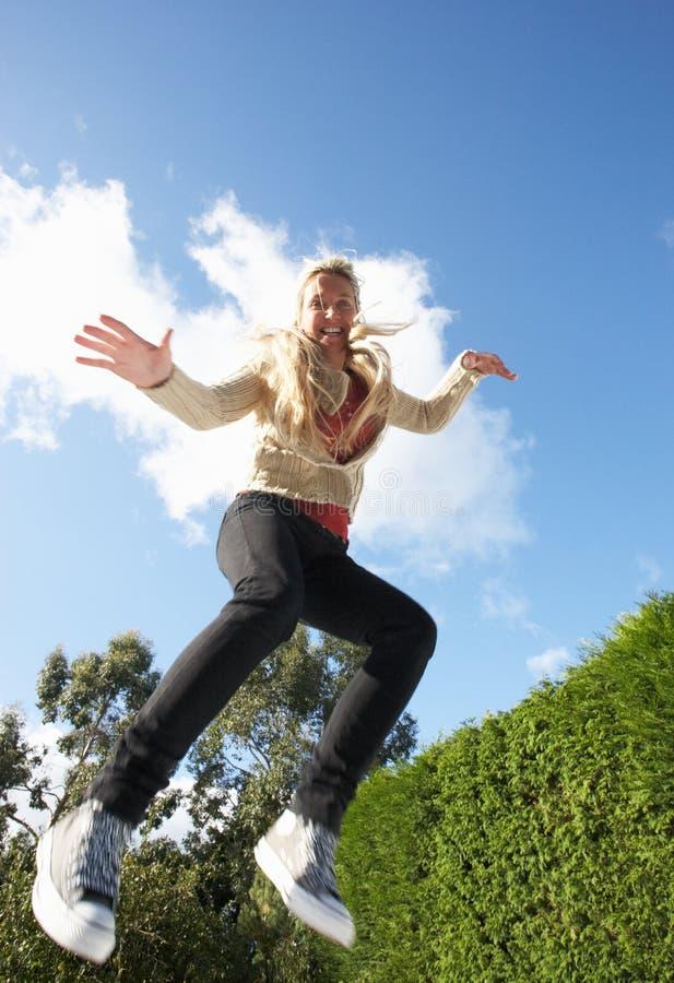 Junge Frau, die auf die Trampoline abgefangen in mittlerem Ai springt stockfotografie