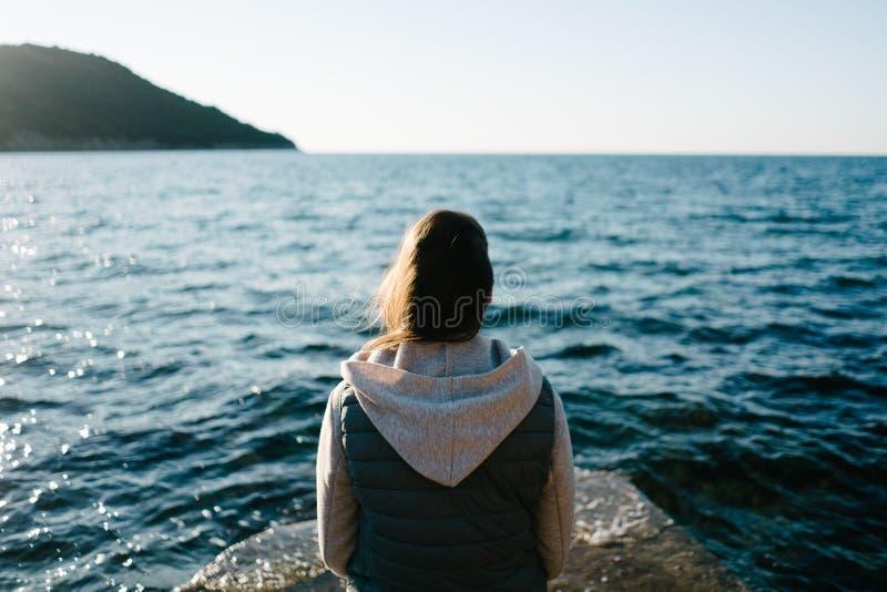 Junge Frau, die auf einem Felsen, anstarrend im Abstand sitzt und schauen im Meer stockbild