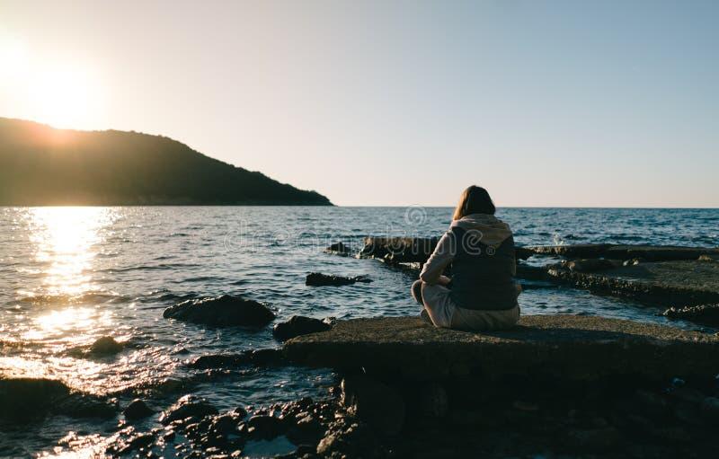 Junge Frau, die auf einem Felsen, anstarrend im Abstand sitzt und schauen im Meer stockfoto