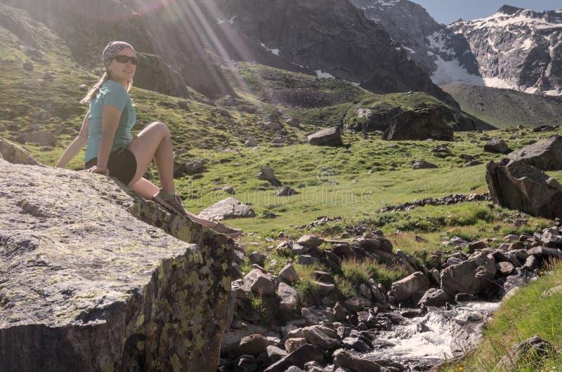 Junge Frau, die auf einem Felsen an den Alpenbergen sitzt lizenzfreie stockfotografie