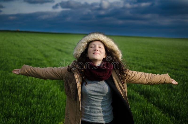 Junge Frau, die auf einem grünen Gebiet mit den Wolken genießen Frischluft glücklich sich fühlt stockfotografie