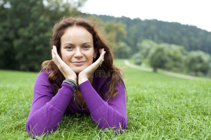 Junge Frau, die auf einem grünen Rasen liegt stockfotos