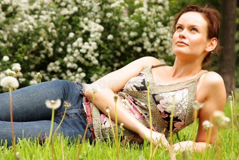 junge Frau, die auf einem grünen Rasen liegt stockbild
