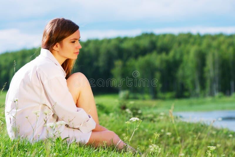 Junge Frau, die auf einem Gras sitzt stockfotografie