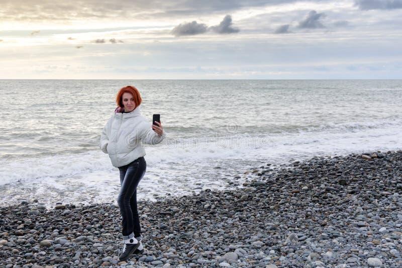 Junge Frau, die auf einem Hintergrund von Meereswellen und von Sonnenuntergang aufwirft und selfie macht lizenzfreie stockfotografie