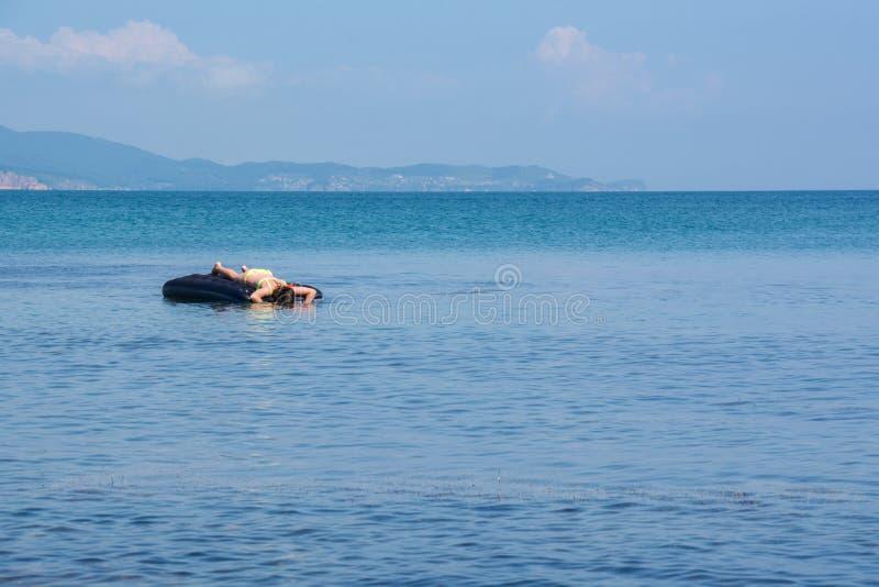 Junge Frau, die auf einem lilo am Swimmingpool sich entspannt stockbilder
