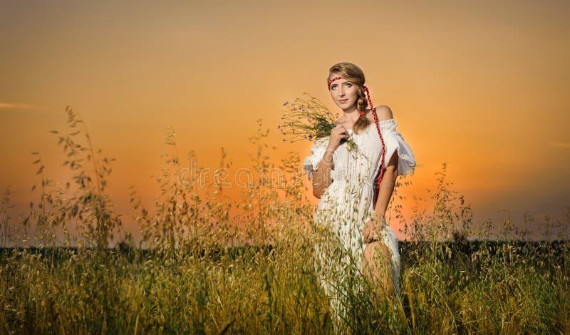 Junge Frau, die auf einem Weizenfeld mit Sonnenaufgang auf dem Hintergrund steht lizenzfreies stockbild