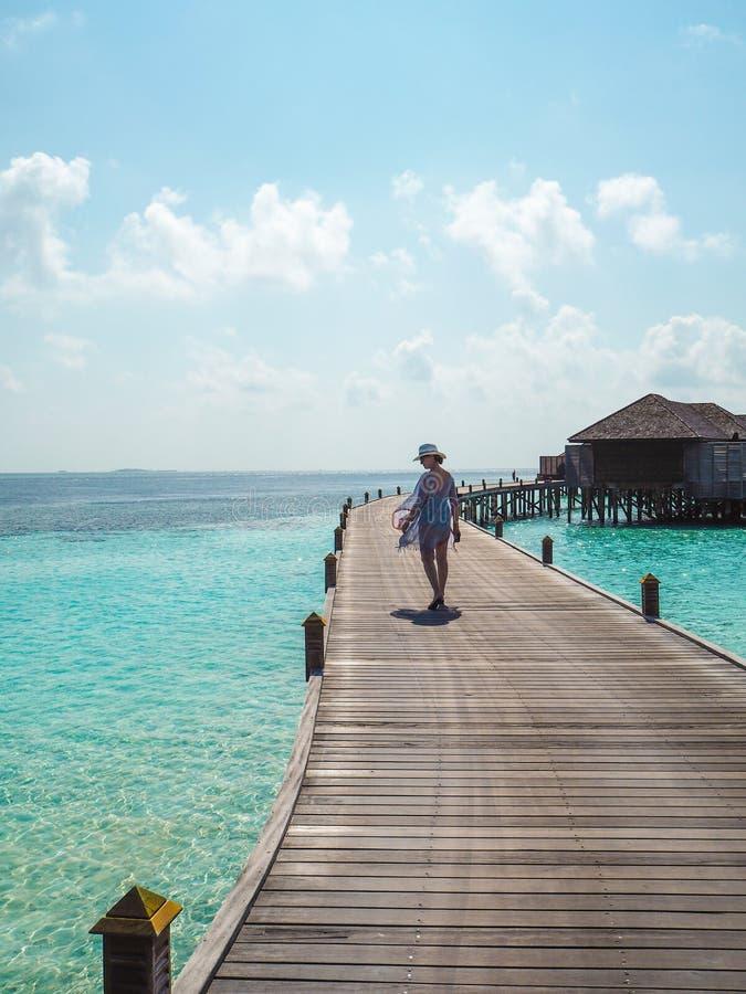 Junge Frau, die auf einen hölzernen Pier in den Malediven schlendert lizenzfreies stockbild
