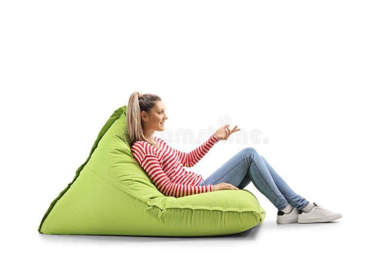 Junge Frau, die auf einer Bohnentasche sitzt und mit der Hand gestikuliert lizenzfreies stockfoto