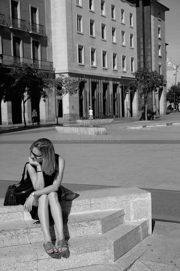Junge Frau, die auf einer Marmor- Bank hält ihr Haupt-withanhand sitzt stockbilder