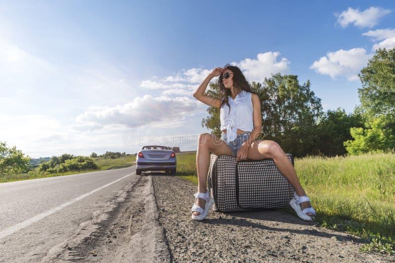 Junge Frau, die auf einer Straße mit Gepäcktasche an den Feldern per Anhalter fährt Mädchen sitzt auf Gepäck und wartet auf das A stockfotos