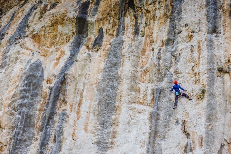 Junge Frau, die auf einer Wand klettert lizenzfreie stockfotos