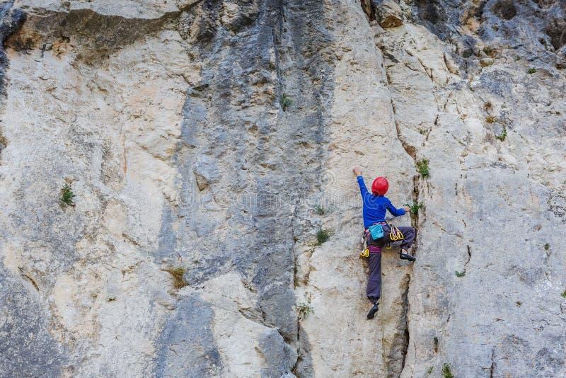 Junge Frau, die auf einer Wand klettert lizenzfreies stockfoto