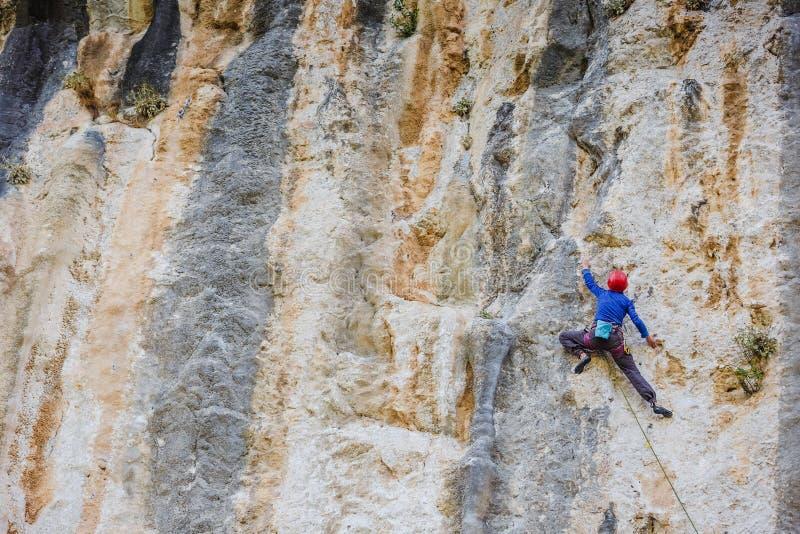 Junge Frau, die auf einer Wand klettert stockbild