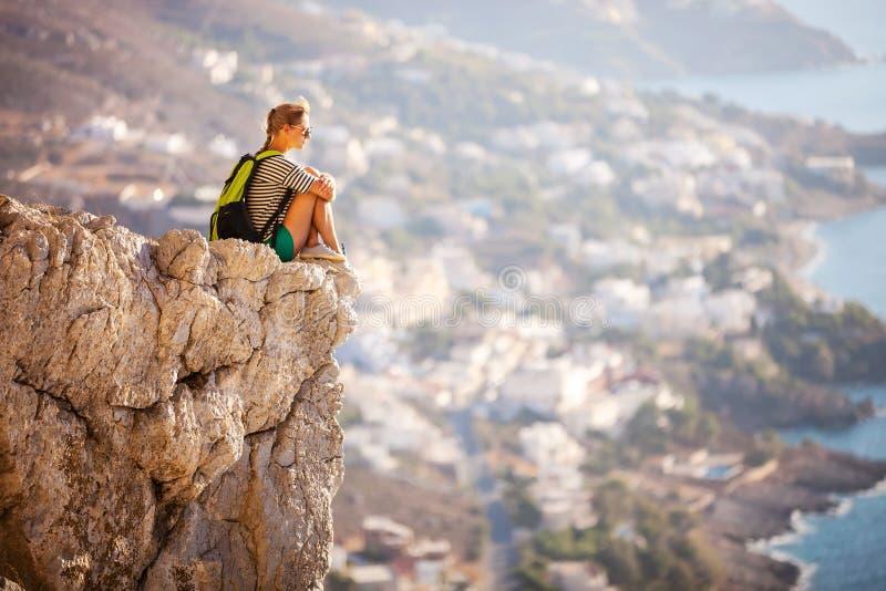 Junge Frau, die auf Felsen sitzt stockfotografie