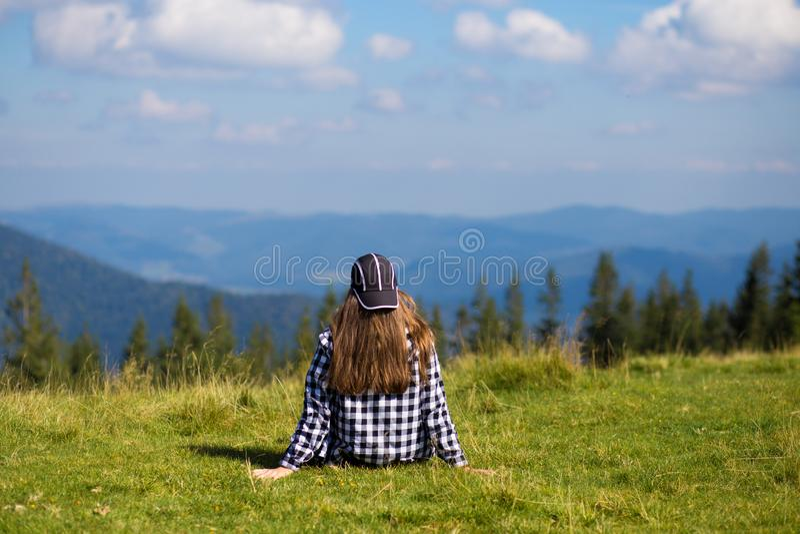 Junge Frau, die auf die Gebirgsoberseite friedlich anstarrt tief liegende Morgenwolken sitzt lizenzfreie stockfotos