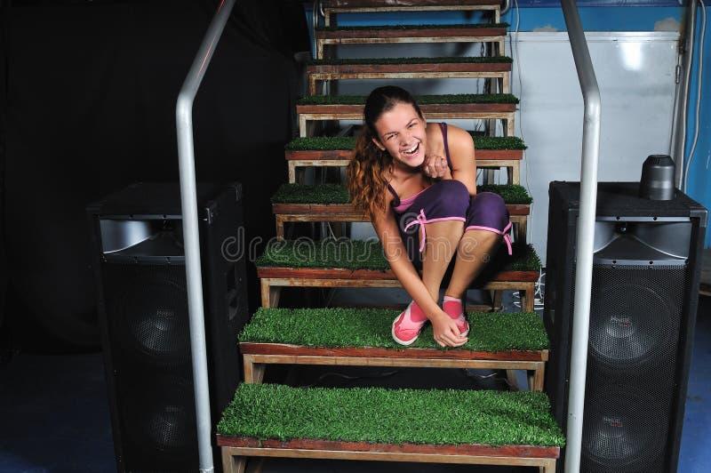 Junge Frau, die auf grünen Treppen lächelt lizenzfreie stockfotografie