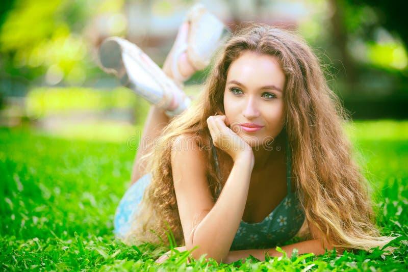 Junge Frau, die auf grünes Gras legt lizenzfreie stockfotografie