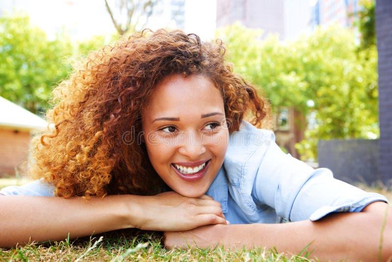 Junge Frau, die auf Gras im Park und im Lächeln liegt lizenzfreie stockfotos