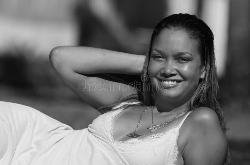 Junge Frau, die auf Gras legt lizenzfreies stockfoto