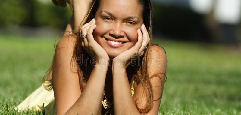 Junge Frau, die auf Gras legt lizenzfreie stockfotos