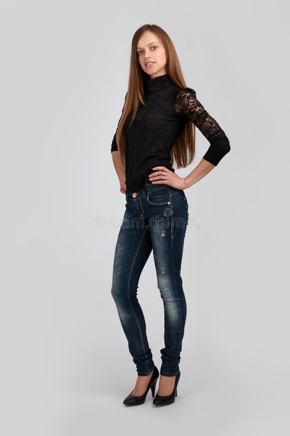 Junge Frau, die auf grauem Hintergrund steht lizenzfreies stockbild