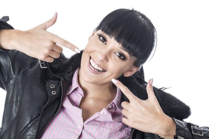 Junge Frau, die auf ihre Zähne oder Lächeln mit beiden Fingern zeigt lizenzfreies stockbild