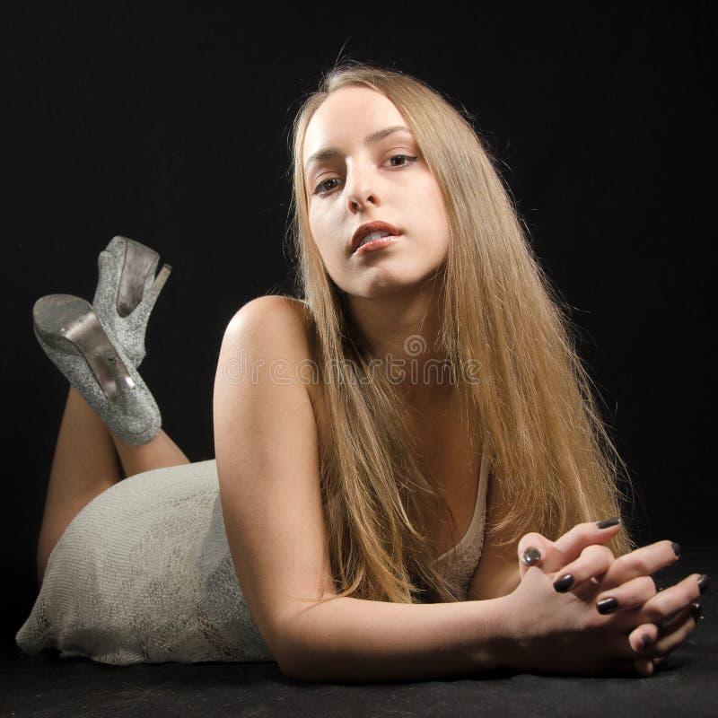 Junge Frau, die auf ihrem Bauch aufwirft stockfoto