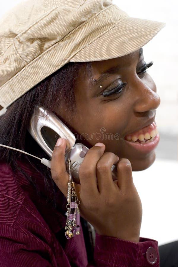 Junge Frau, die auf ihrem Mobiltelefon spricht stockfotografie