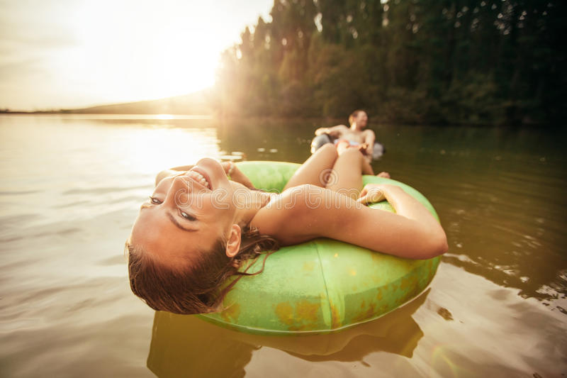 Junge Frau, die auf innerem Rohr im Wasser sich entspannt lizenzfreies stockbild