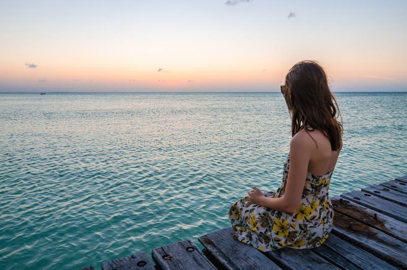 Junge Frau, die auf Küstenanlegestelle bei Sonnenuntergang sitzt lizenzfreies stockbild