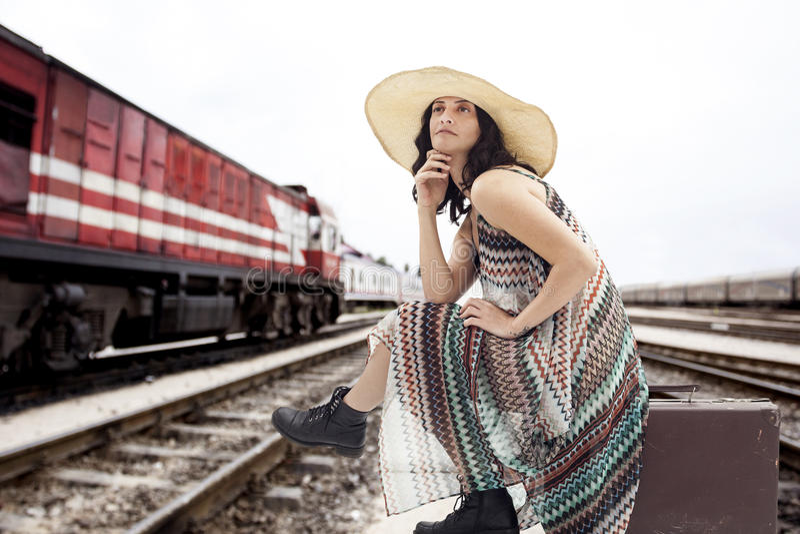 Junge Frau, die auf Koffer sitzt stockfotografie